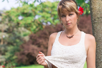 Attractive young woman in garden or park with red rose