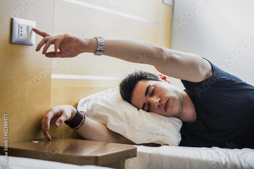 Tired Guy Switching off Light While Lying on Bed