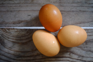 three fresh eggs on the wooden table