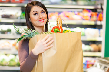 Smiling woman holding a bag full of vegetables