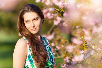 Beautiful  brunette woman in blooming orchard