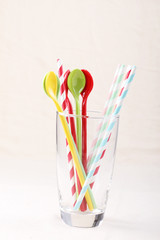 colorful spoon and stripped straw in clear glass