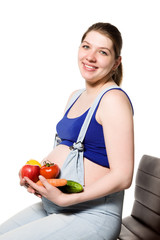 Pregnant caucasian woman holds vegetables and fruits