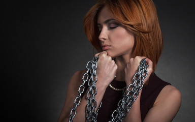 Portrait of a elegantly dressed young women chained.