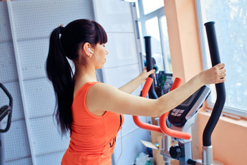Girl exercising at the gym on stepper machine