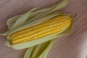 Corn cobs on wood background