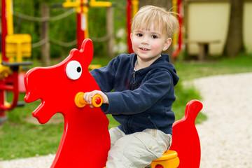 blond boy playing on playground
