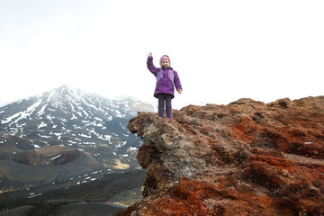 Girl celebrating reached summit of crater on Mount Etna