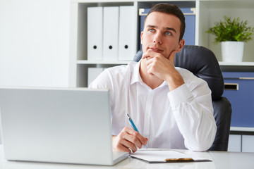 Pensive young businessman with notebook