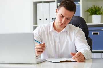 Young businessman signs a document