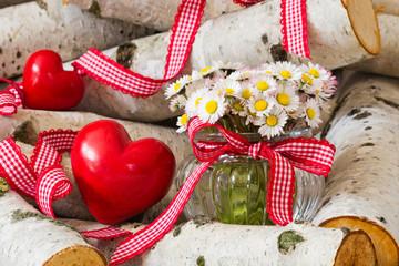 Gänseblümchen und Herzen zwischen Birkenstämmen