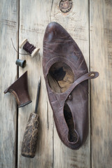 Old worn shoes on a wooden table. Top view