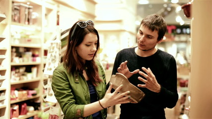 happy young couple choosing dishes in shopping mall shop