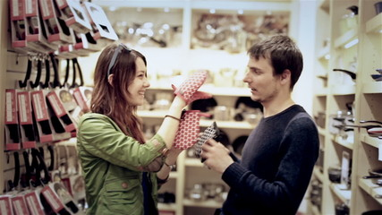 Young attractive couple have fun in mall. Wear kitchen potholder