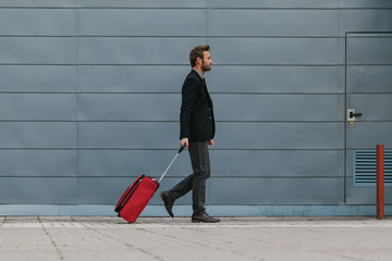 Businessman with a Red Suitcase at the Airport