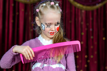 Girl with Face Painted Brushing Hair with Big Comb