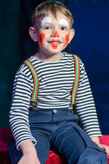 Cute excited little boy in comic red makeup