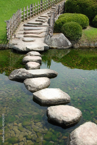 Leinwandbild Motiv Bridge made of stones in a Japanese garden