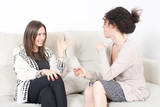 Zwei glückliche Frauen im Gespräch auf Sofa