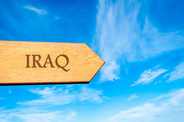Wooden arrow sign pointing destination IRAQ