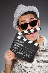 Young camera assistant with clapperboard