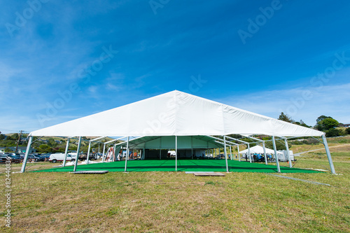 Huge white tent with green floor in field