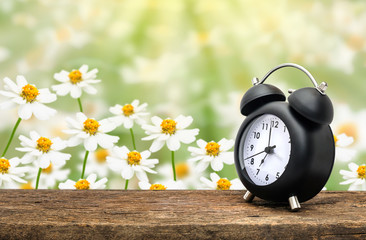 Clock on wood table over flower in background