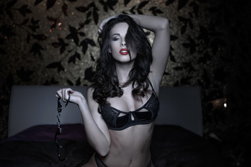 Sexy woman posing with handcuffs in bed