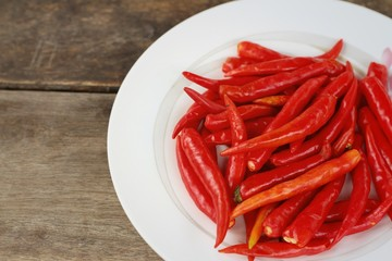 Chilies in white dish on a background of wood