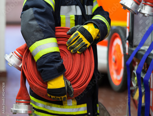 Leinwanddruck Bild Feuerwehrmann Feuerwehrwache mit Wasserschlauch in der Hand