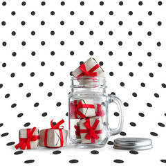 Mason jar filled with small gift boxes.