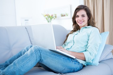 Happy brunette using her laptop on couch