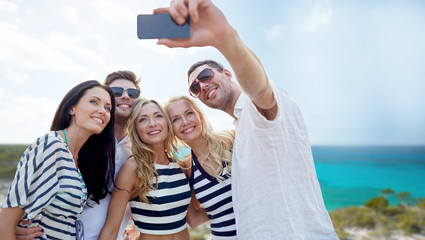 friends on beach taking selfie with smartphone