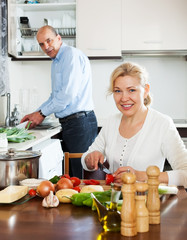 happy mature couple cooking Spaniard tomatoes