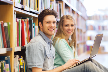 happy students with laptop in library