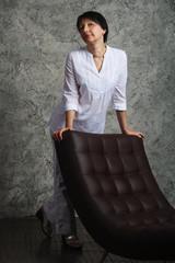 Женщина в белом рядом с креслом