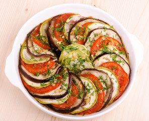 ratatouille vegetables baked layers, top view on a wooden table