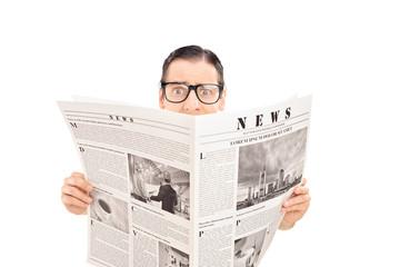 Terrified man reading a newspaper