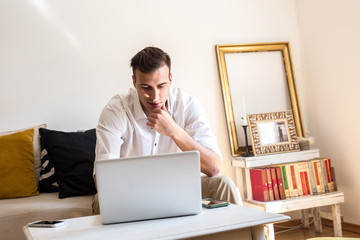 Young man sitting in his living room and using laptop