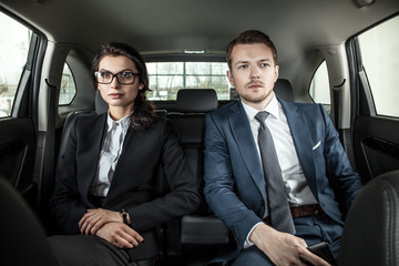 businessman and businesswoman sitting in a limousine.