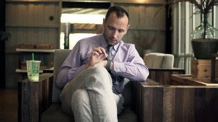 Young businessman with smartwatch sitting in cafe