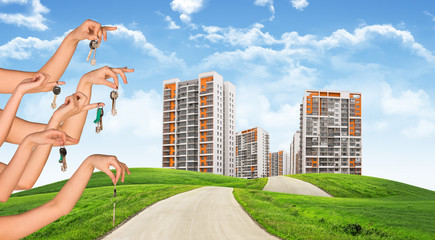 Cityscape under blue sky with keys in hands