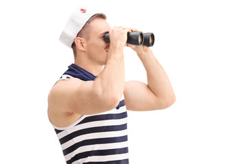 Young male sailor looking through binoculars