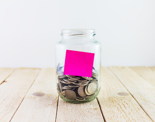 Coins in a glass jar with sticky note on white background