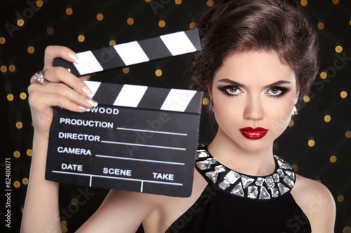 Poster Beautiful brunette woman model holding film clap board cinema. F