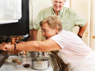 senior couple cooking in kitchen