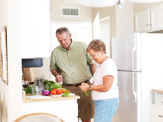 elderly husband and wife making dinner together in kitchen