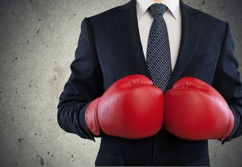 Boxing. Businessman in boxing gloves on background