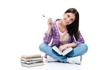 Smiling woman sitting on the floor with books