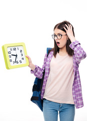 Surprised young female student looking on clock